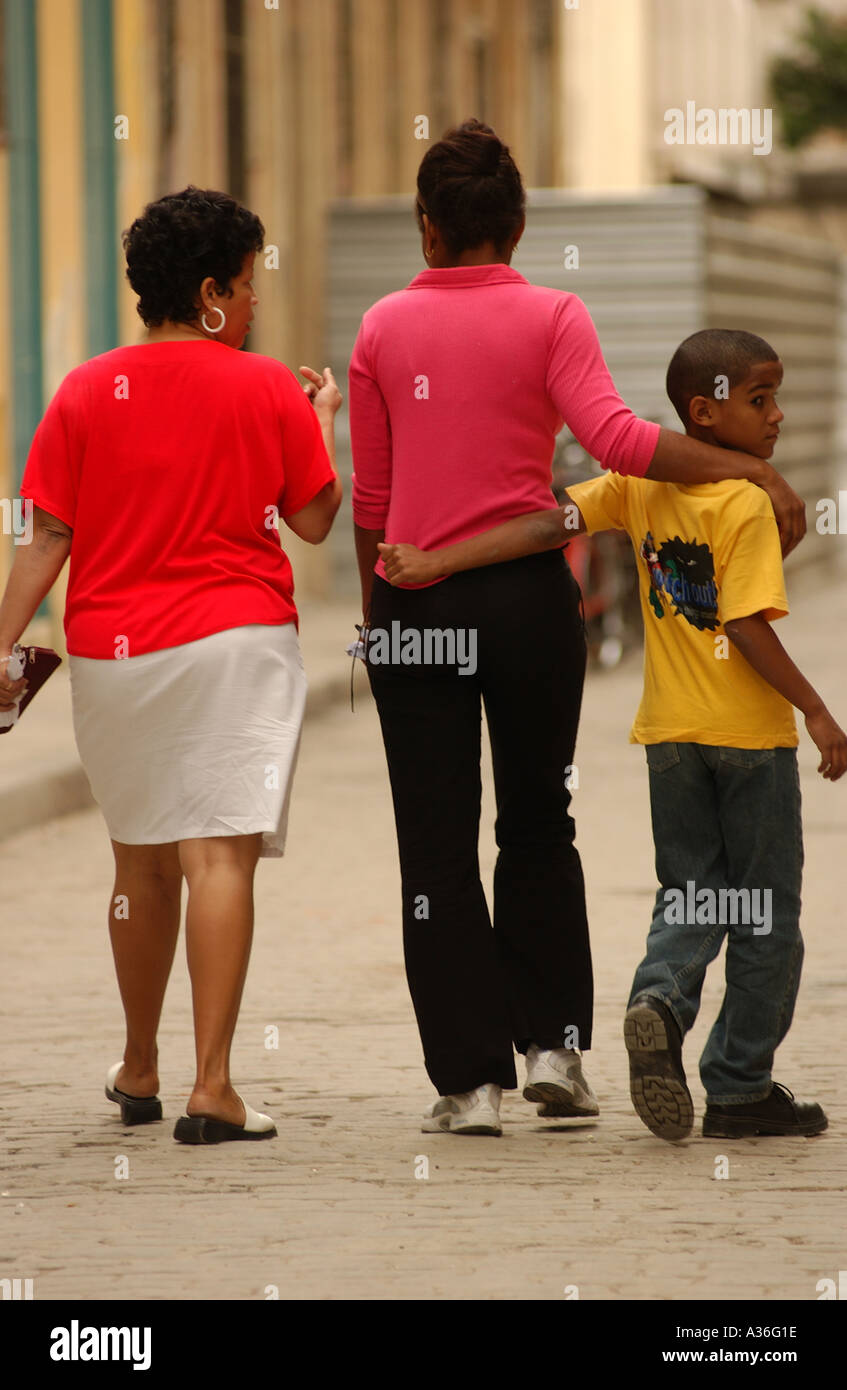 Rear view of a mother with her daughter and son walking on the street Havana Cuba - Stock Image