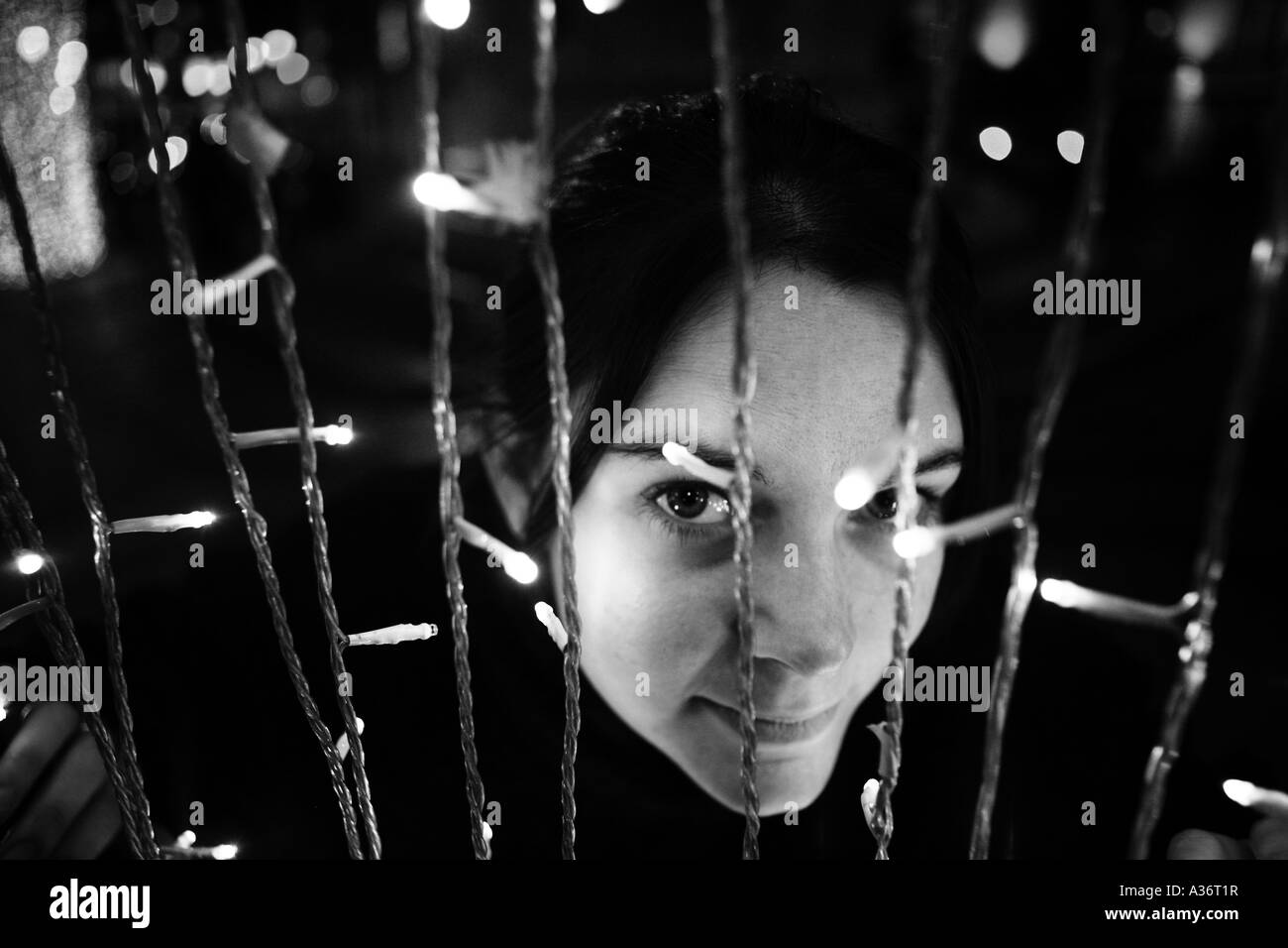 a lady looking though hanging christmas lights in lisbon portugal stock image