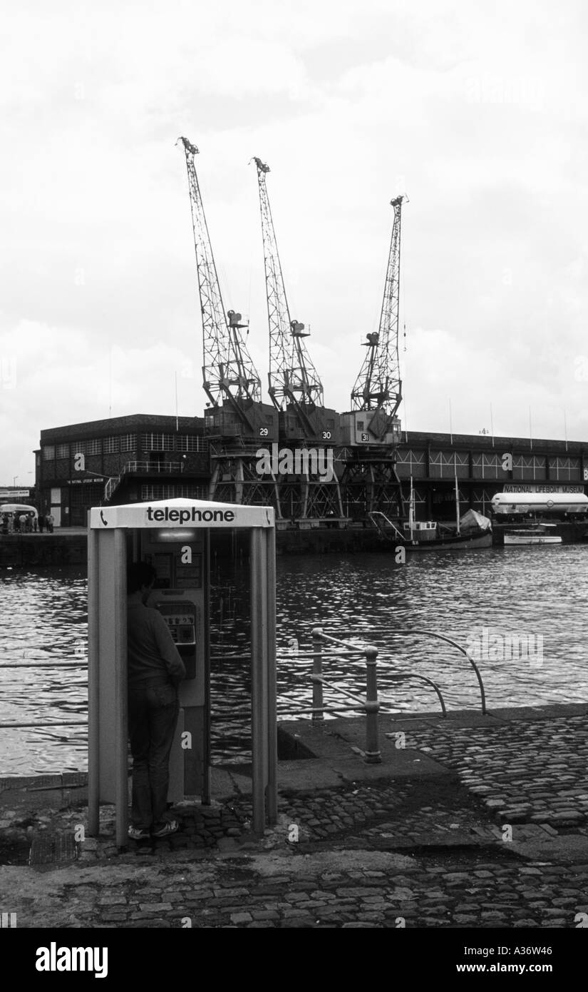 Black and white of a man in a telephone box on a dockside - Stock Image