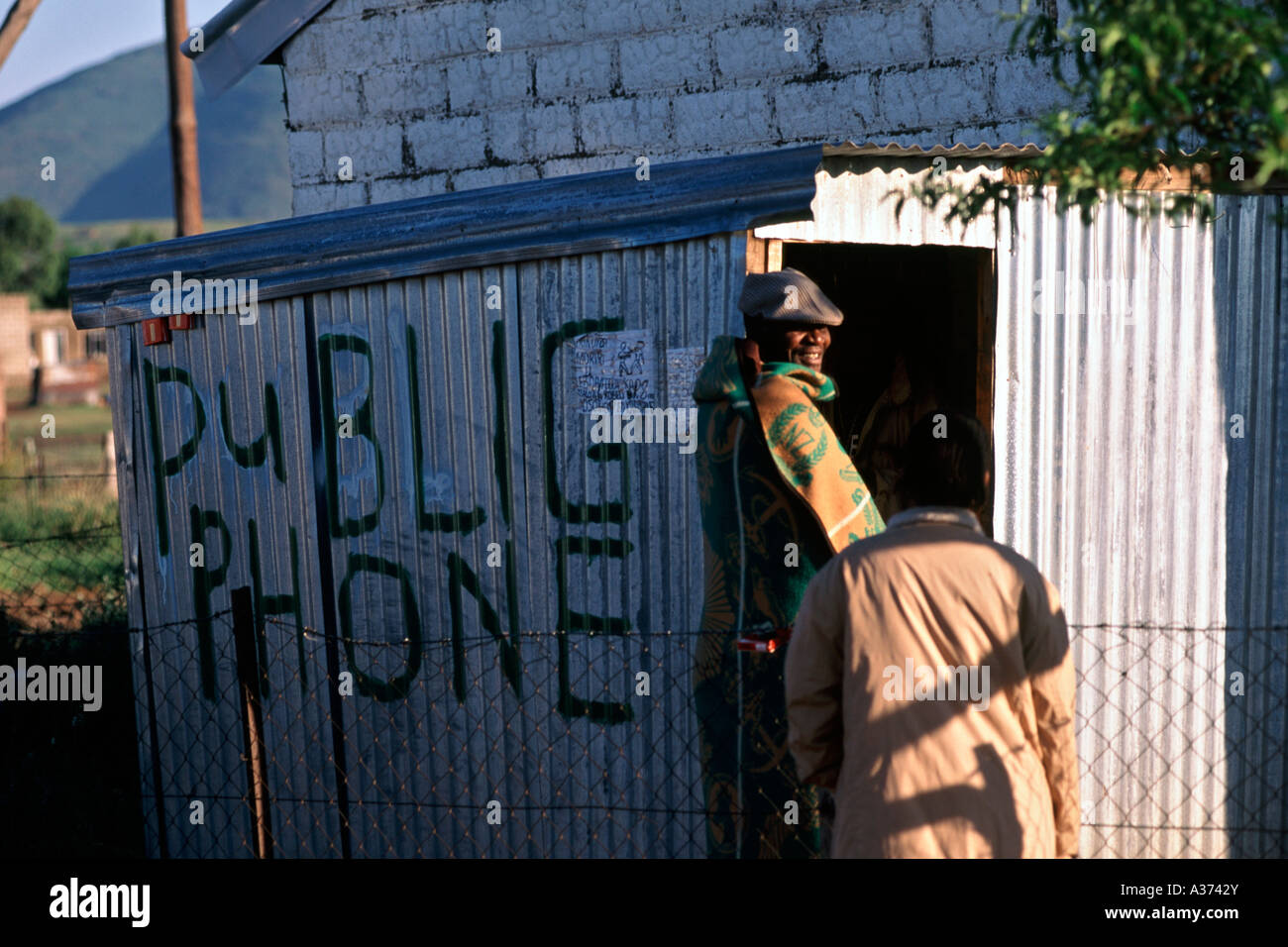 Basotho villagers from Semonkong queue to use a telephone in a makeshift public telephone kiosk in the mountains - Stock Image