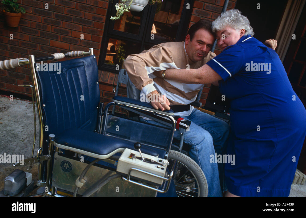 District Nurse helps disabled man into his wheelchair on a visit to his home in London UK - Stock Image