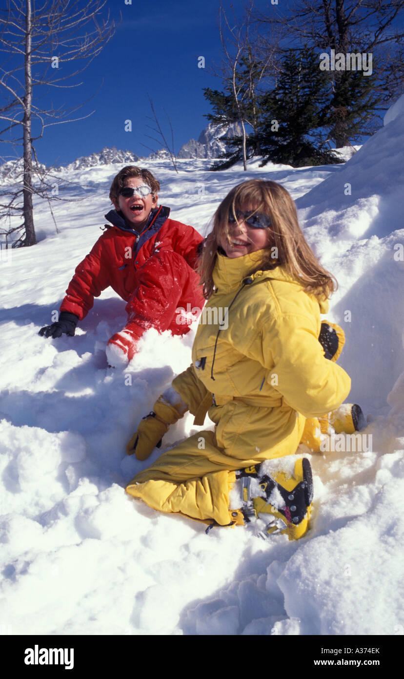Two children in ski suits playing in the snow - Stock Image
