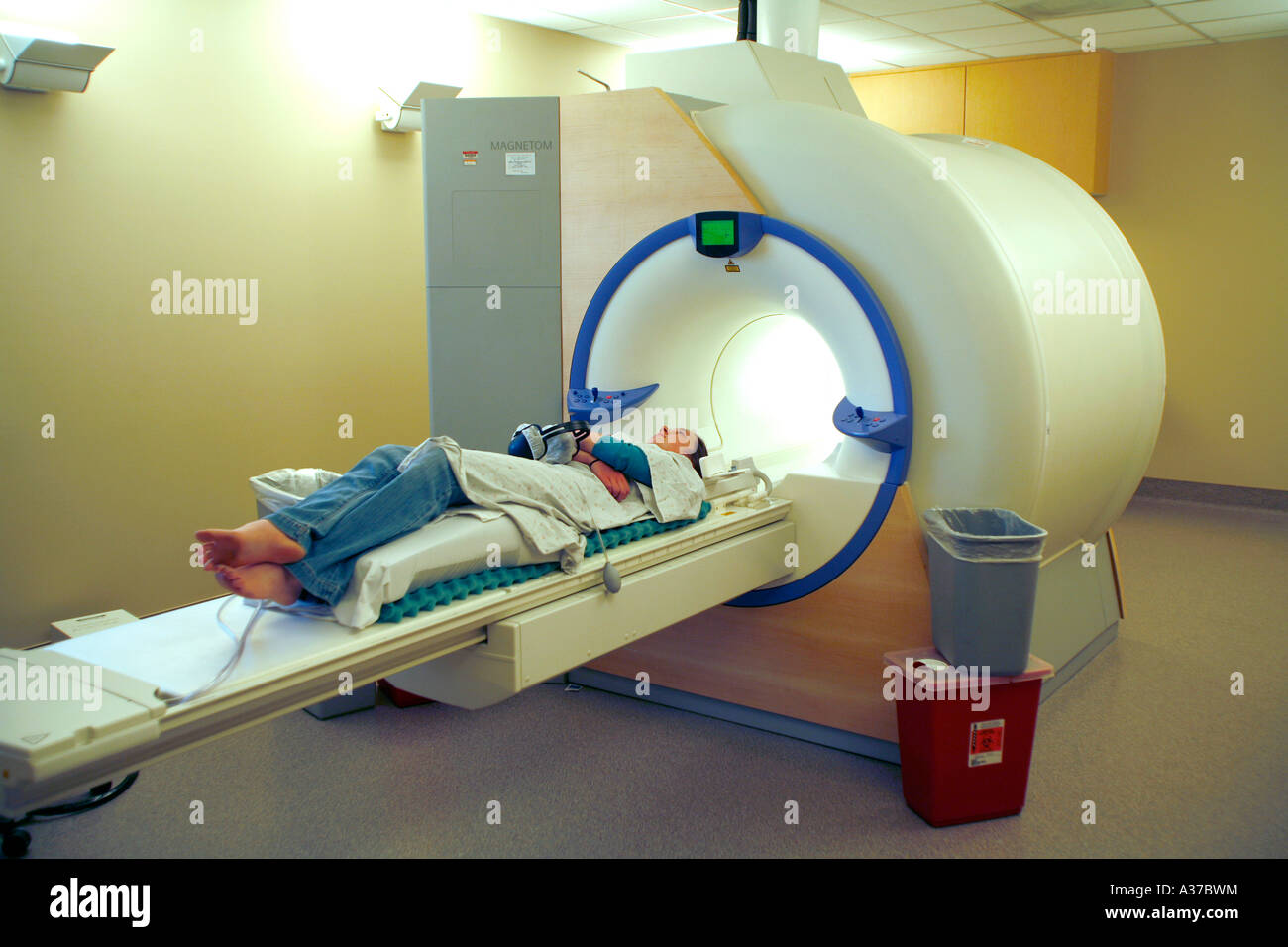 An MRI (Magnetic resonance imaging) machine is being used to test a teenage female for the reason she has head aches. - Stock Image