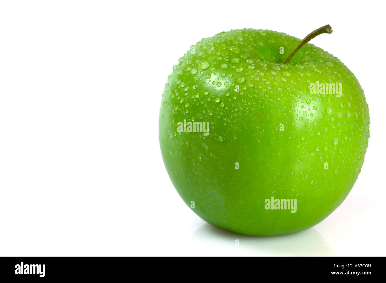 Green apple covered in water droplets isolated against a white background. Slight shadow detail for realism. Stock Photo