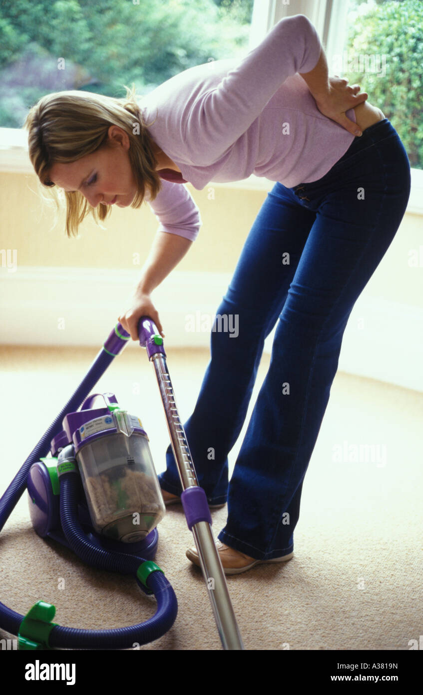 woman with backache from vacuuming - Stock Image