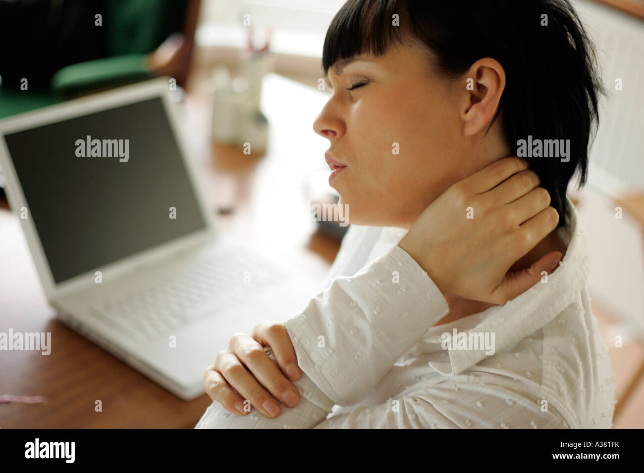 woman with sore shoulder from using the computer - Stock Image