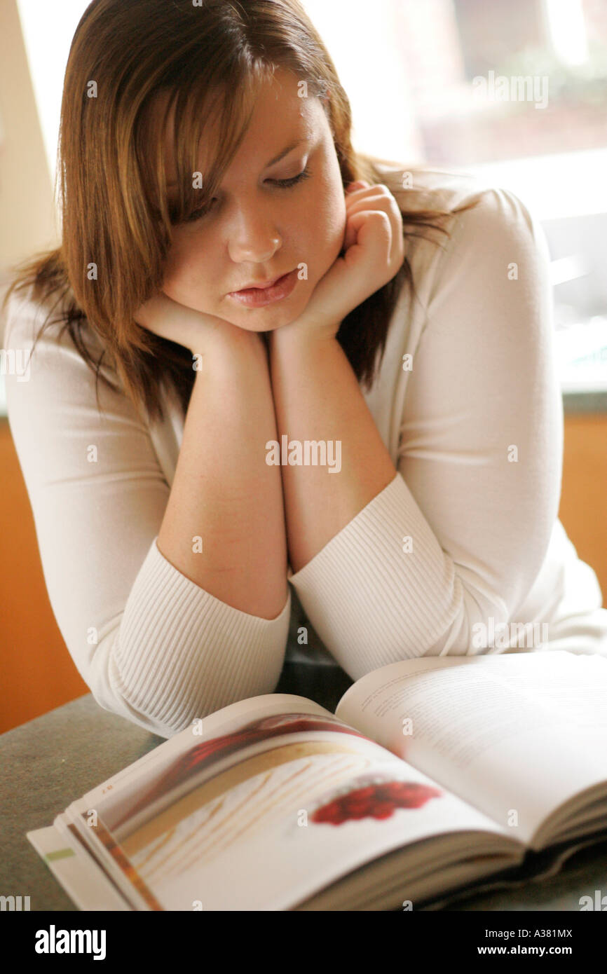 plump woman reading cookery book - Stock Image