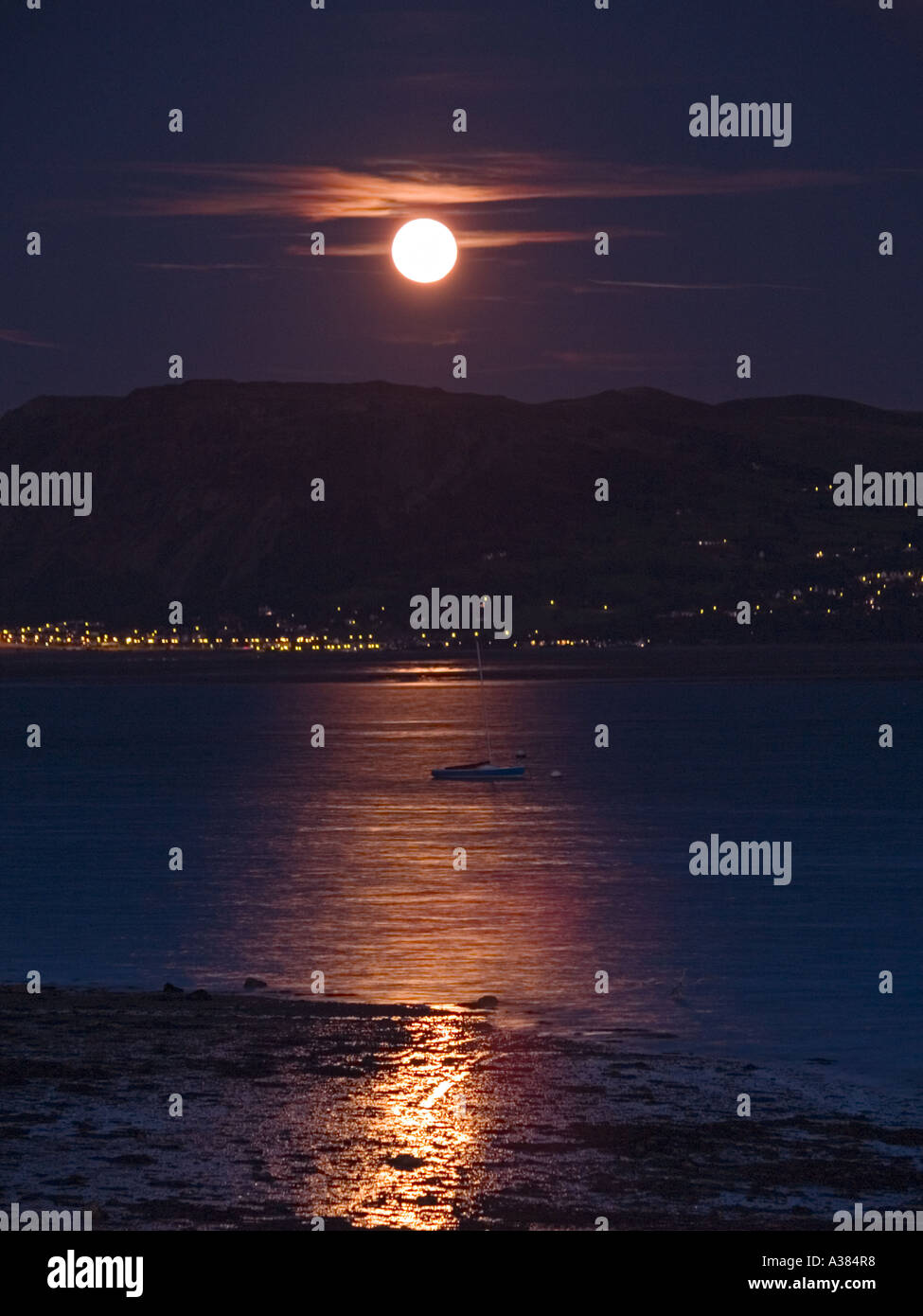 MOON RISE over MENAI STRAIT with full moon above Tal y Fan from Beaumaris Anglesey North Wales UK - Stock Image