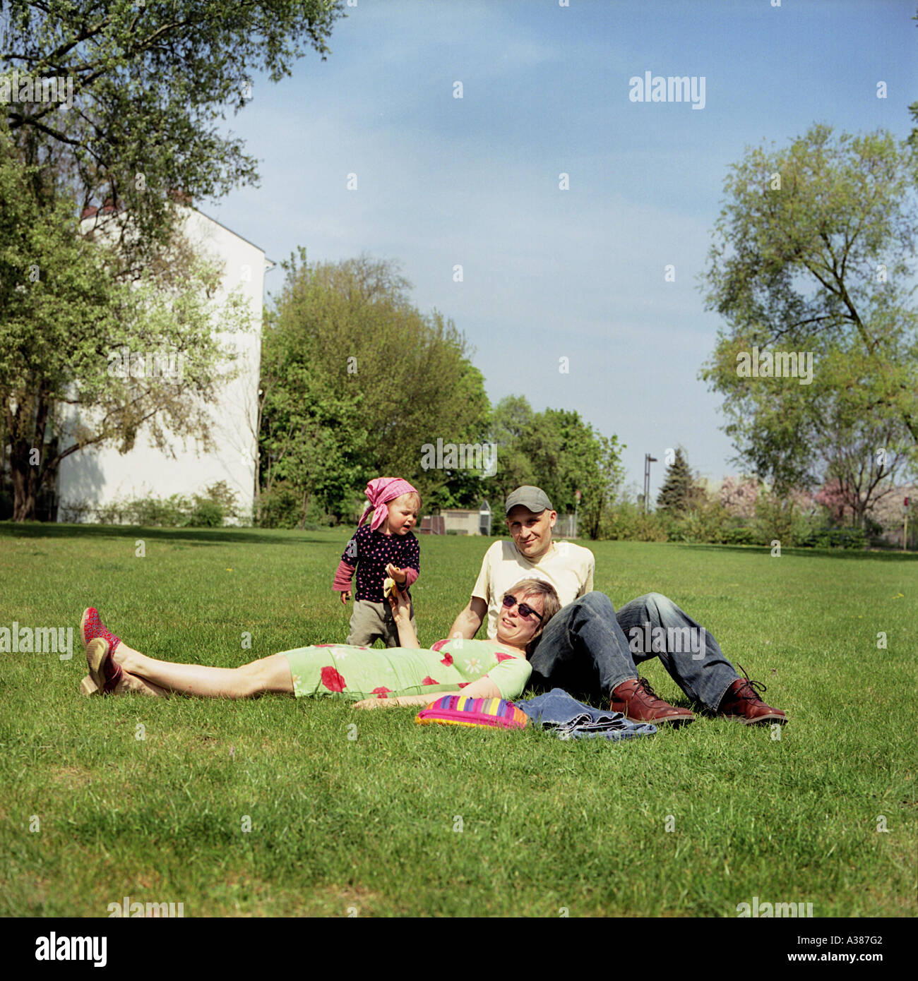 family with child on green grass in Berlin - Stock Image