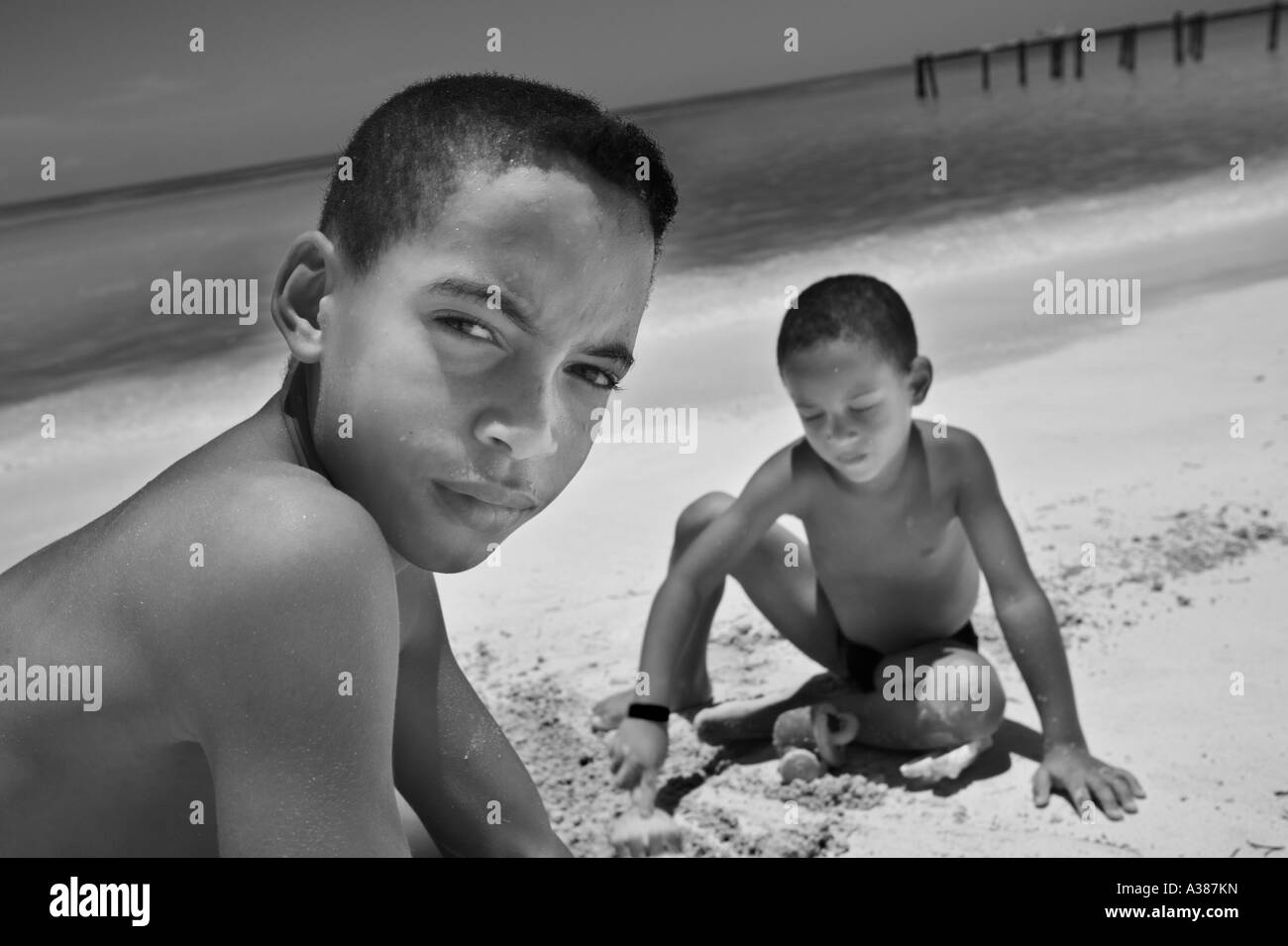Two Cuban boys play in the sand at Playa Ancon a popular vacation beach town near Trinidad - Stock Image
