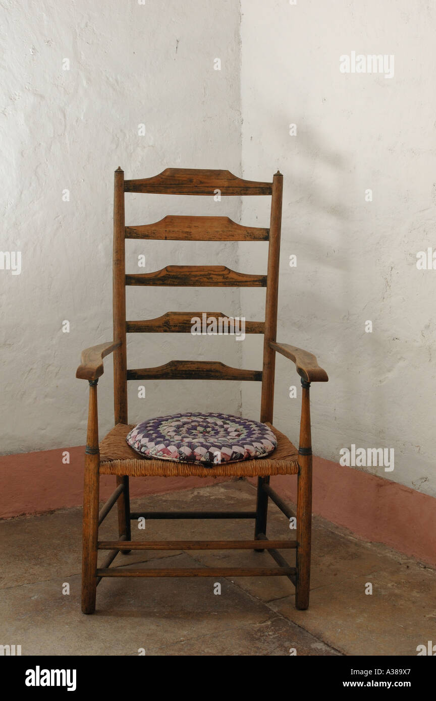 Antique English ladderback chair in corner of room with whitewashed walls and stone floor Stock Photo