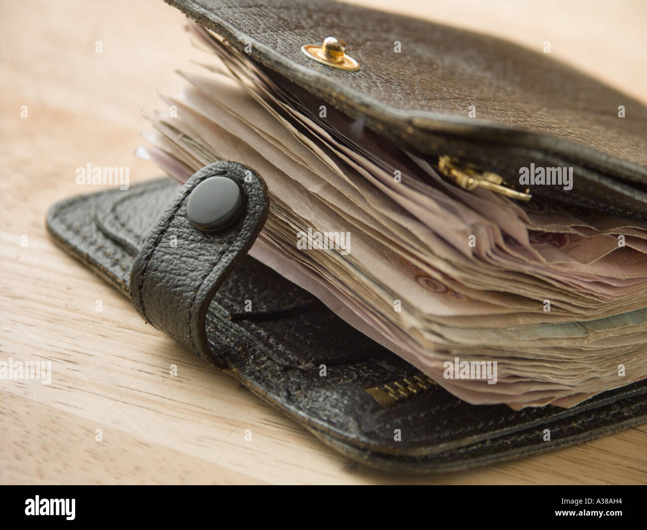 A wad of money in a black leather wallet - Stock Image