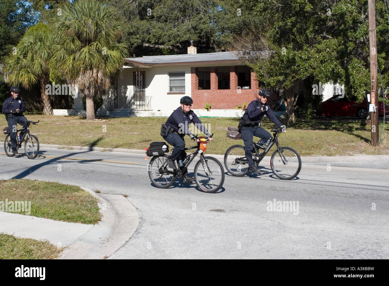 Two Bicycle Policeman Patrolling on a Residential Street Stock Photo