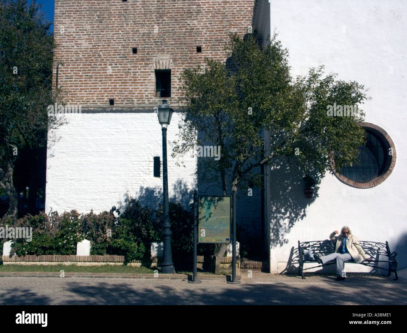 Woman rests on Bench outside the Church of the Immaculate Conception rest resting reclining sitting bench 16th 16 Stock Photo