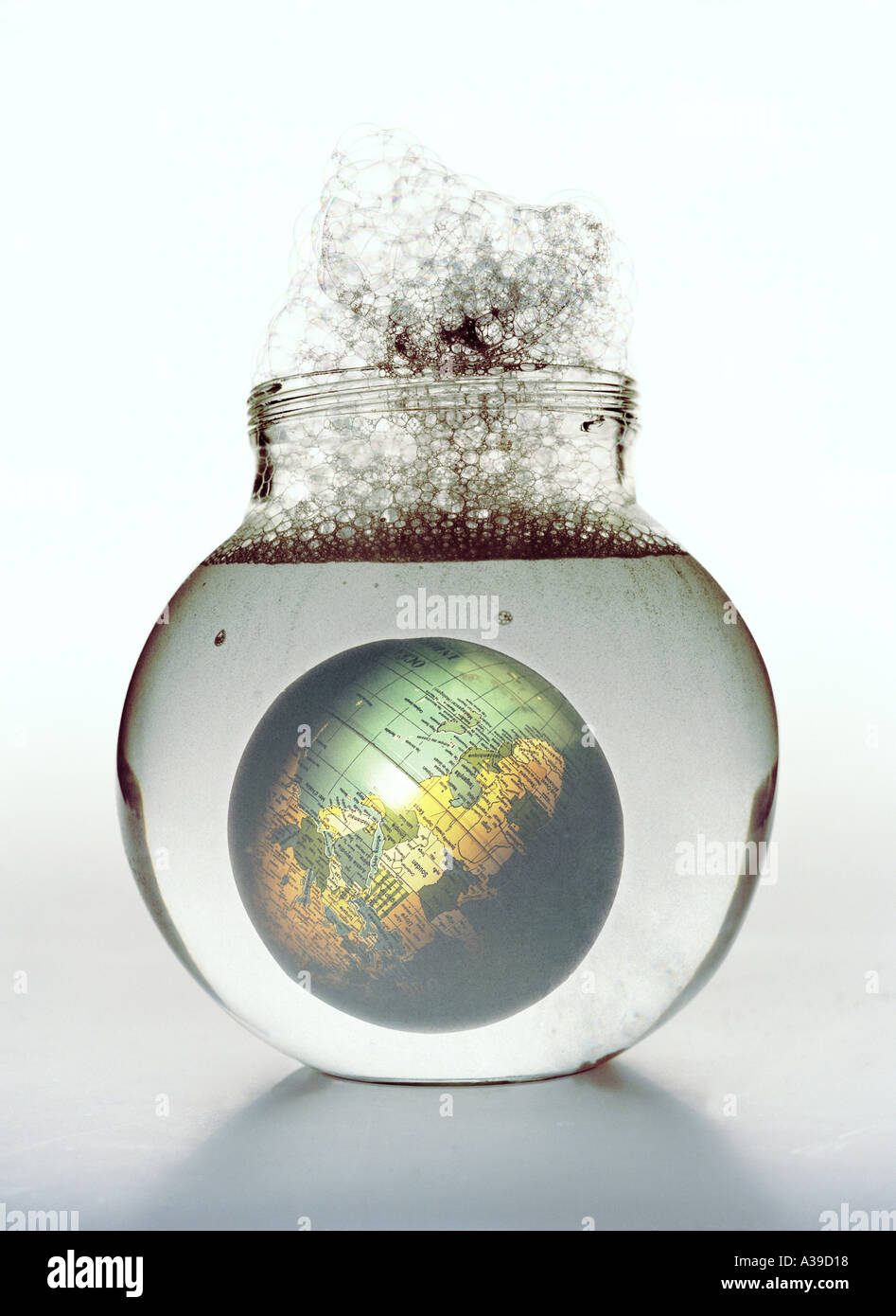 Globe in Foaming Fluid Symbol for Pollution of the Environment Stock Photo