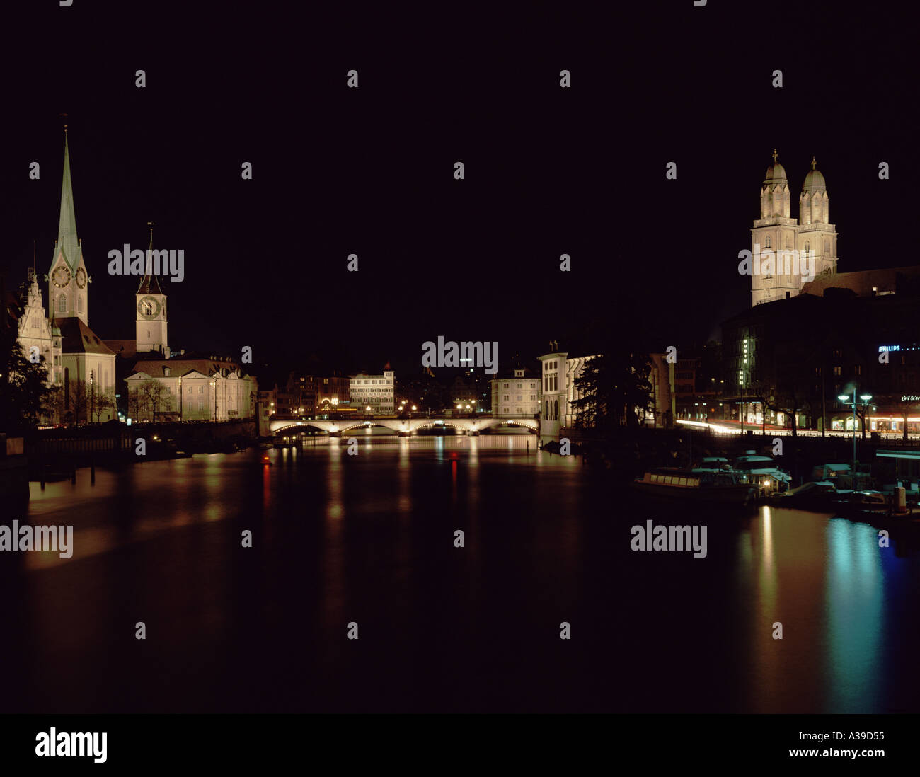 Church Grossmünster to the right River of Limmat City of Zurich Downtown at Night Canton of Zurich Switzerland - Stock Image