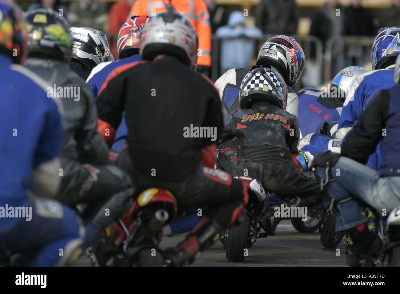 Senior minibike competitors rear view as the field takes a corner at demonstration Motorcycle and motorsport show - Stock Image