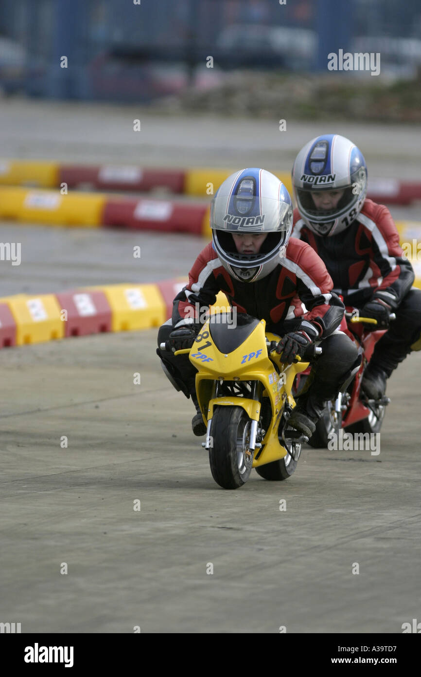 Two junior minibike competitors at demonstration Motorcycle and motorsport show Titanic Quarter Belfast Northern Ireland - Stock Image