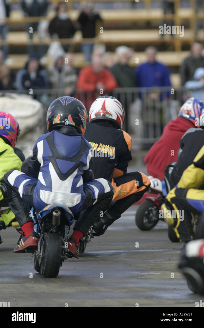 Junior minibike take a corner behind angle at demonstration Motorcycle and motorsport show Titanic Quarter Belfast - Stock Image