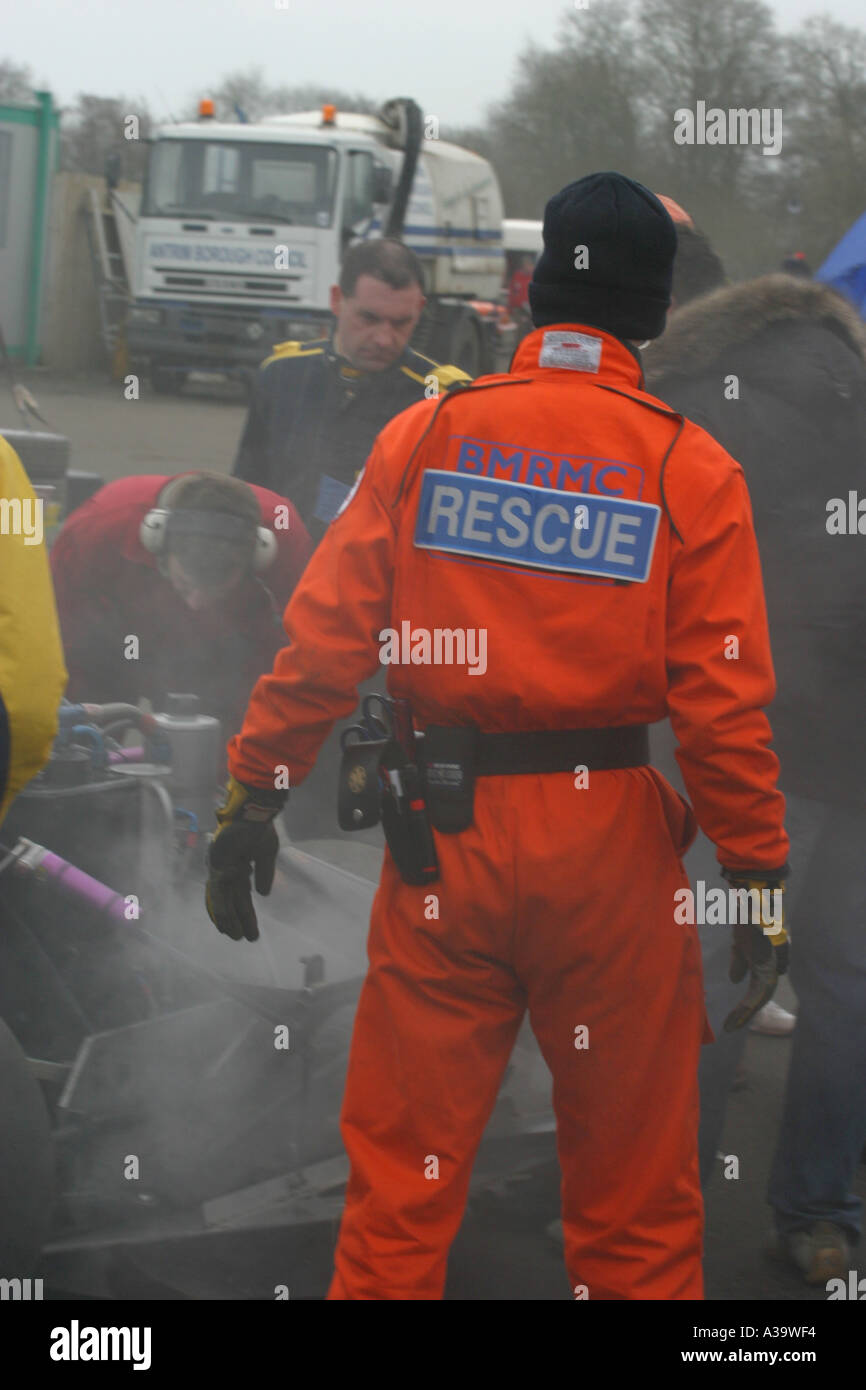 Motorsport emergency rescue marshall looks on as rally cross car on fire is extinguished Nutts Corner motorsport circuit - Stock Image