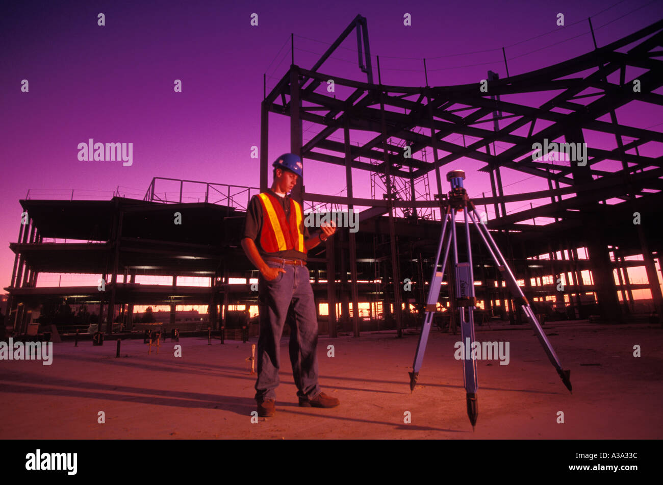 surveyor using GPS surveying device at construction site of steel
