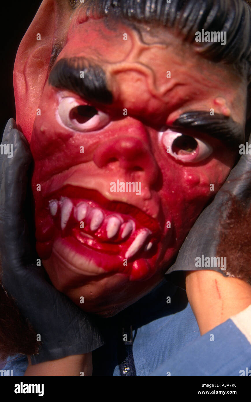 child wearing scary halloween face mask and hands in hairy gloves holding head with teeth and fangs
