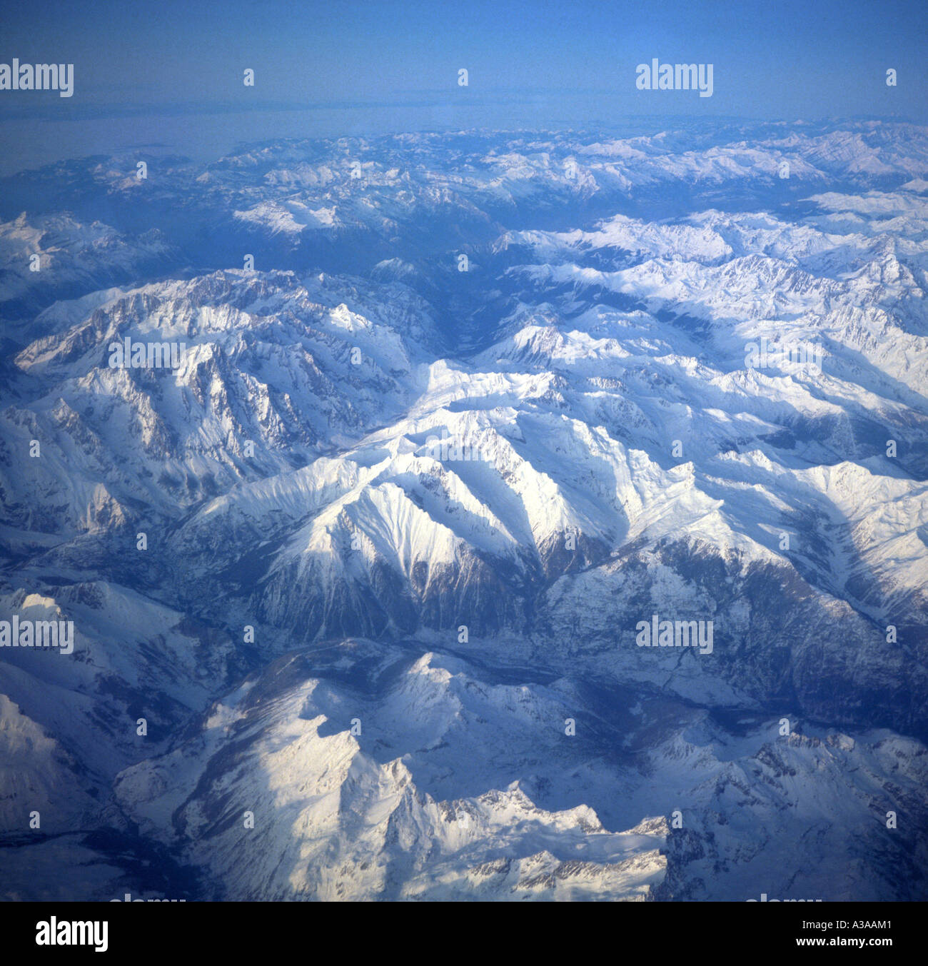 Aerial view of alpine mountain peaks covered by ice and snow - Stock Image