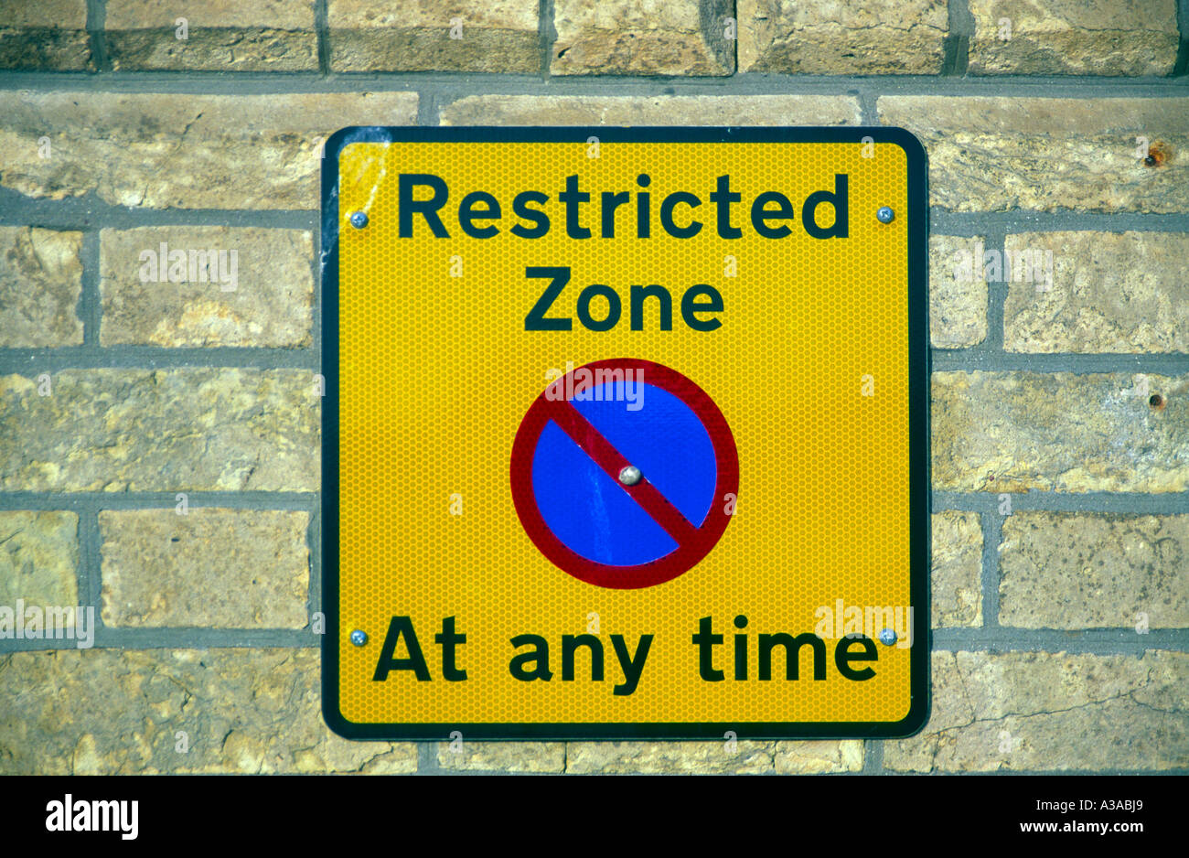 Restricted zone yellow rectangular no parking street sign fixed on brick wall - Stock Image