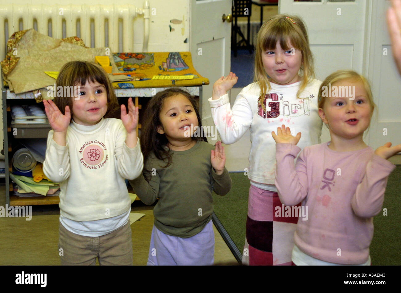 nursery school girls clapping and singing in class. - Stock Image