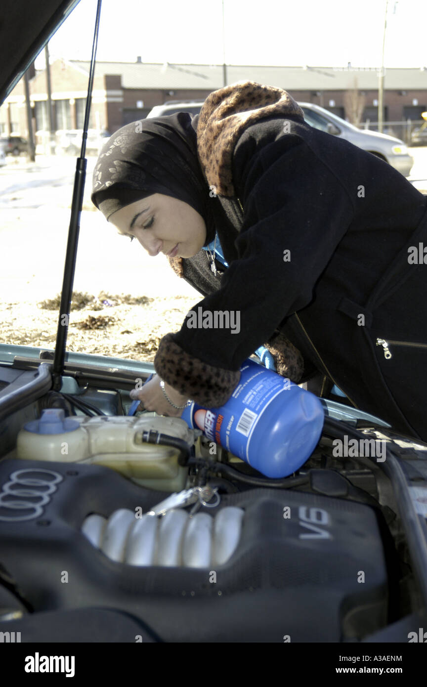 P11 095 Arab Woman Wearing a Hejab Fills Audi Automomobile with Wiper Fluid in Dearborn, MI Stock Photo