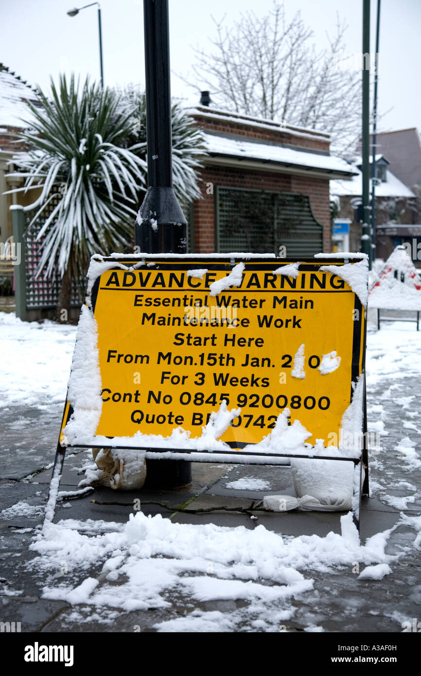 Advance road work warning sign in the snow UK Stock Photo