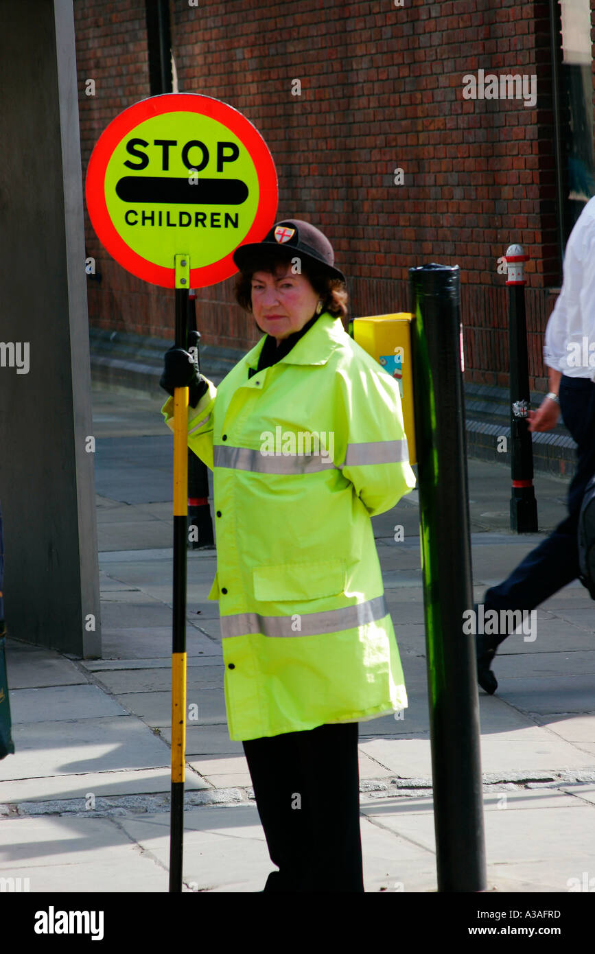 A British Lollipop Lady crossing guard helping children cross a busy road  in London UK -