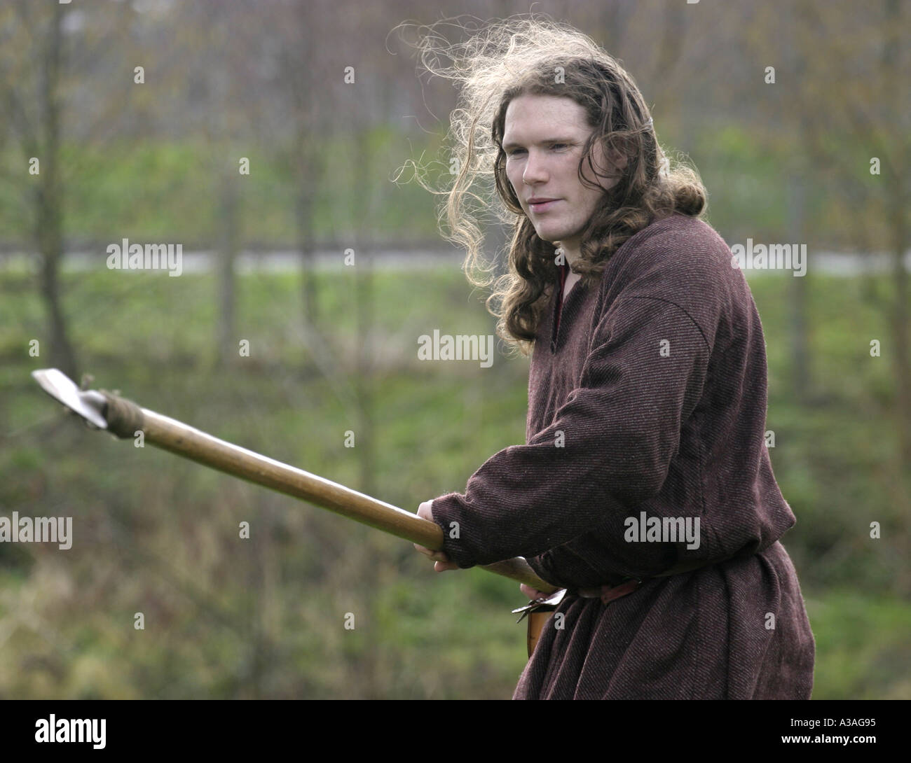iron age reinactor role player in costume with long spear pointing ecos centre ballymena st Patrick s day county antrim - Stock Image