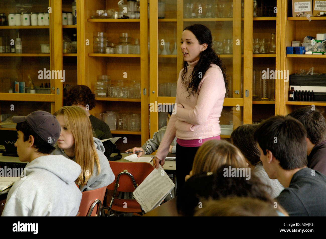 Young female teacher interacting with high school secondary students in classroom - Stock Image