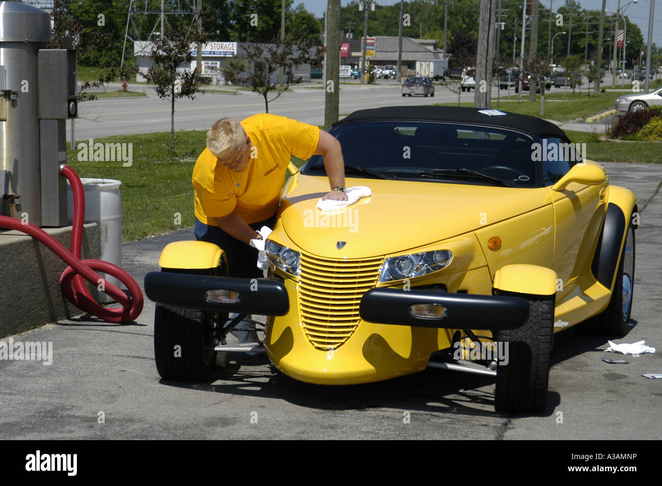 P20 142 Man In Yellow Shirt Washes His Yellow Dodge Prowler Automobile 1 - Stock Image
