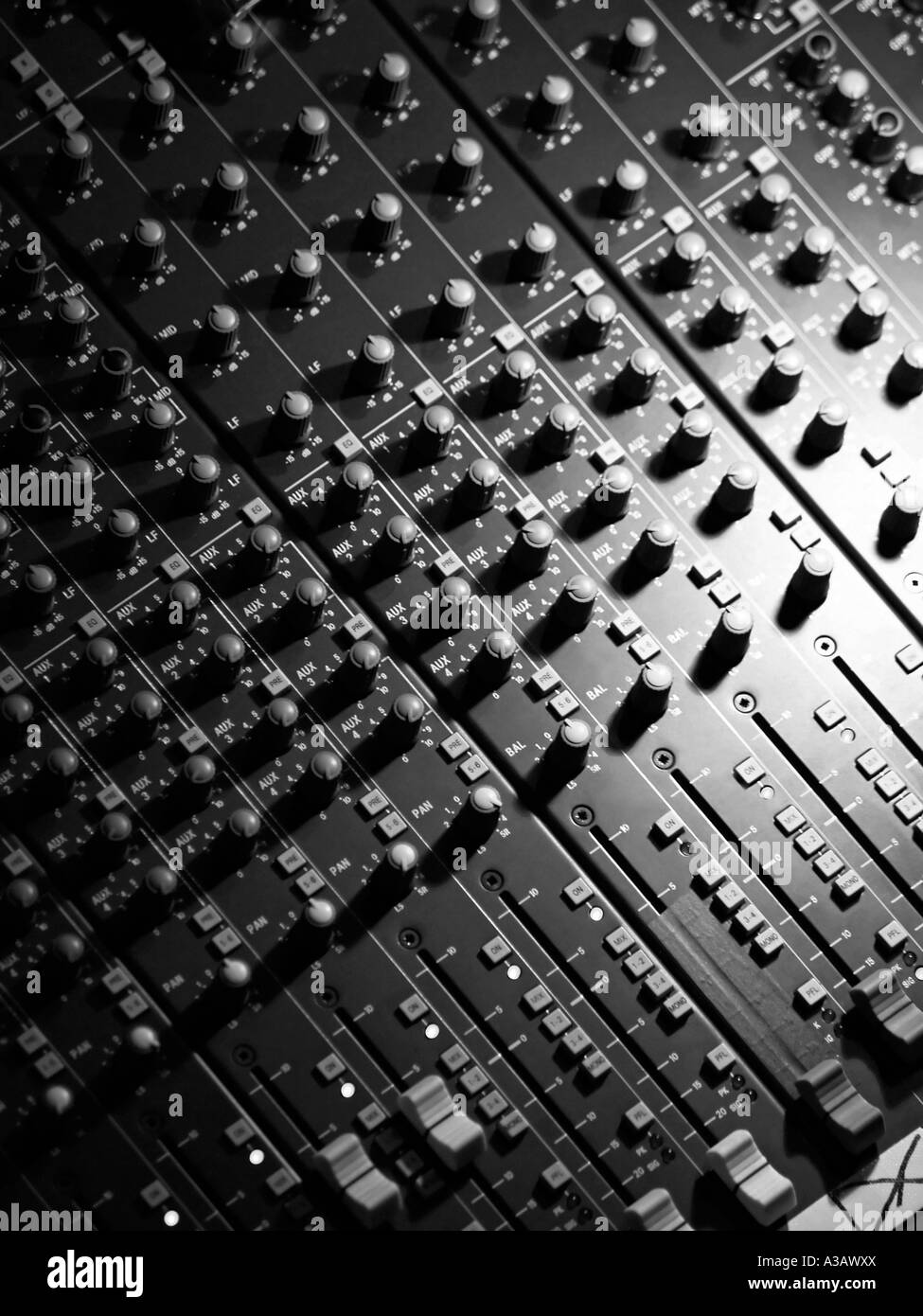 Black and white image of music sound mixing table panel with many knobs buttons switches sliders and other controls - Stock Image