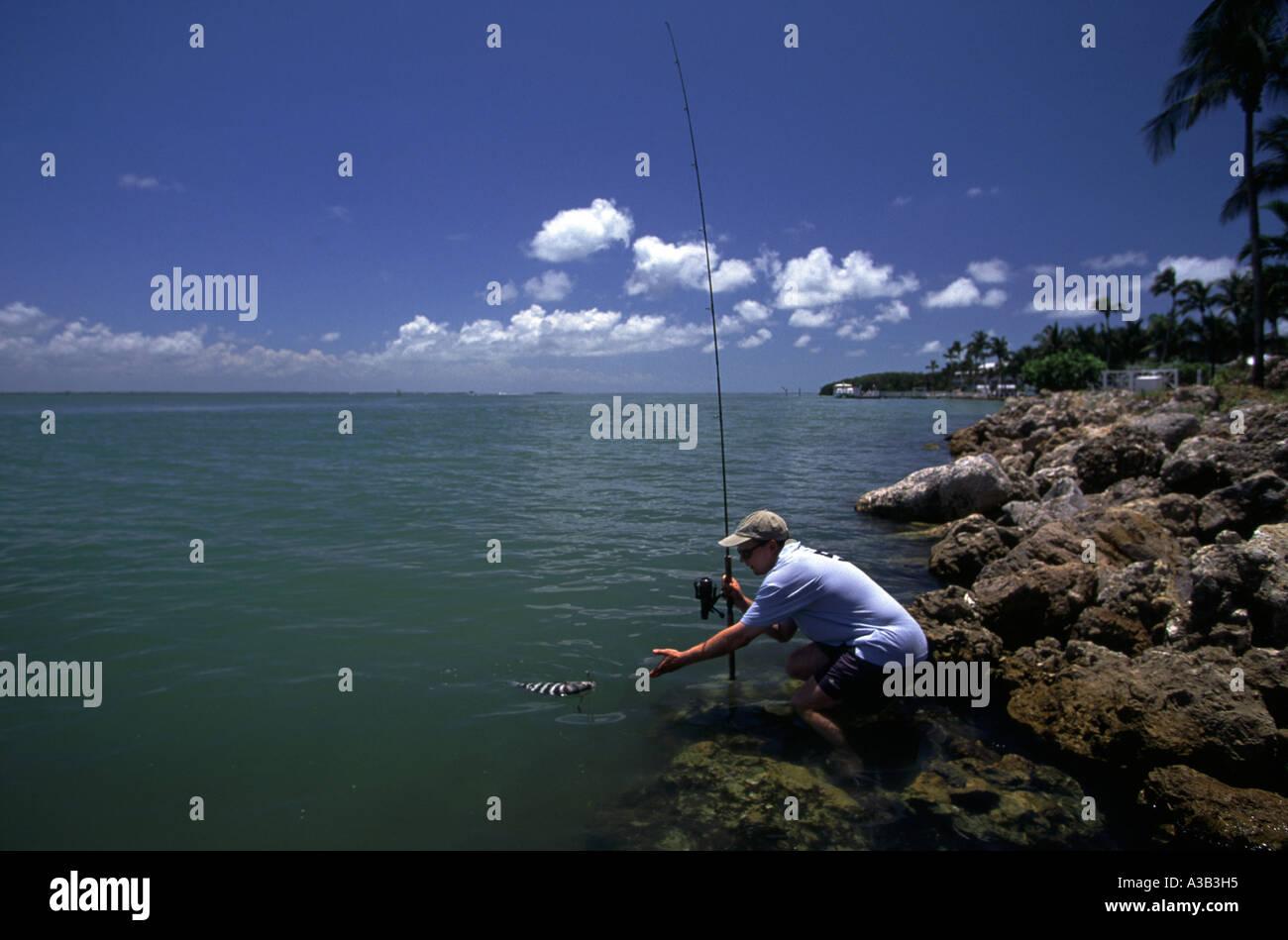 A MAN CATCHES A FISH CAPTIVA ISLAND FLORIDA Stock Photo