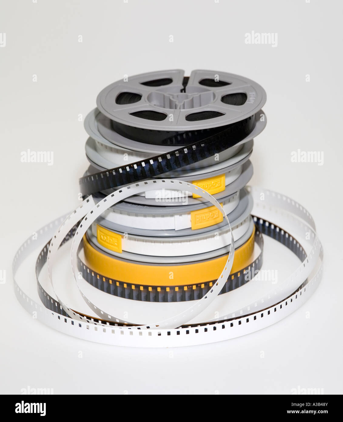Stack of amateur 8mm cine film reels with one spool unwound to show the film and leader - Stock Image