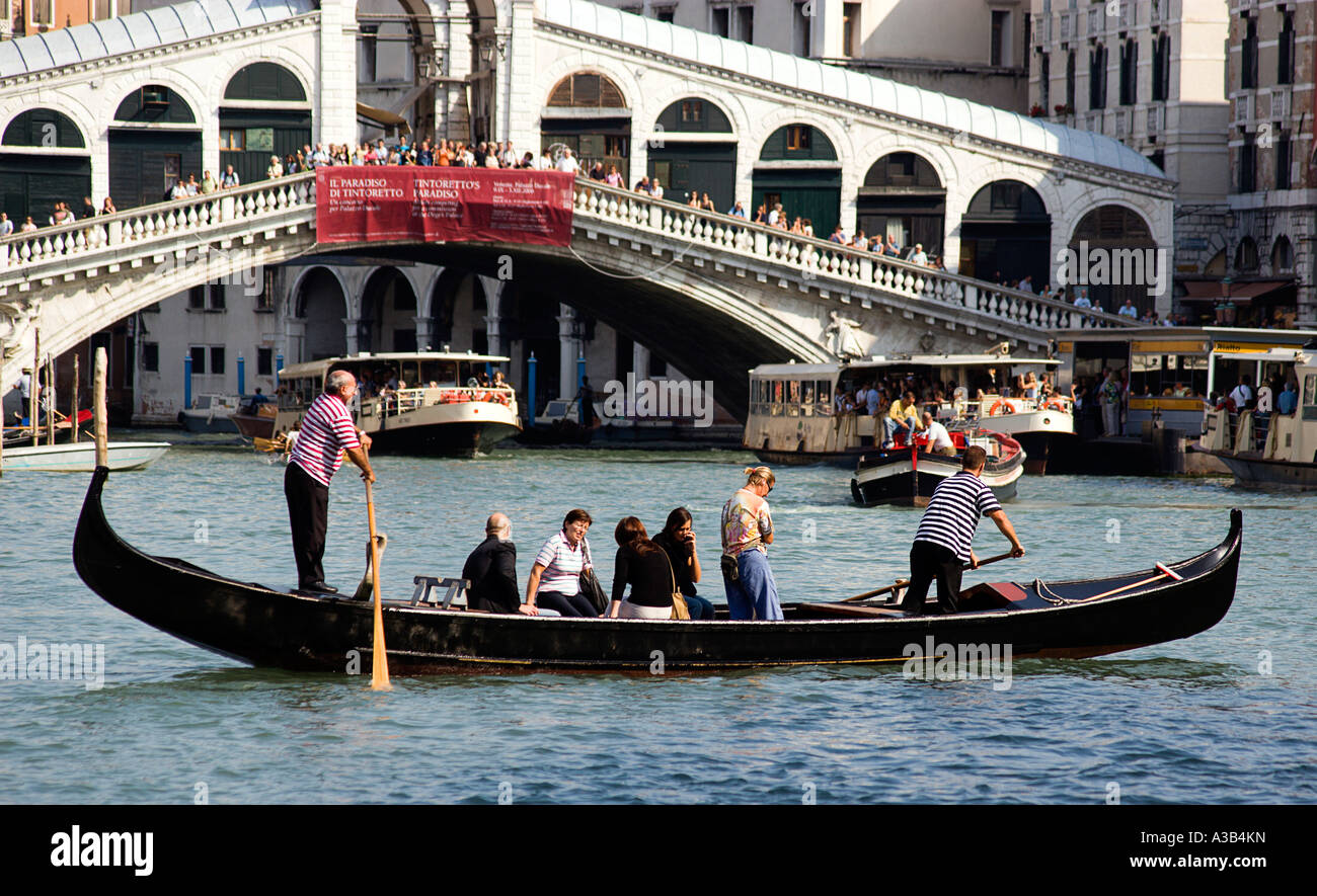 ITALY Veneto Venice A Traghetto gondola carrying local people on board crosses Grand Canal by Rialto Bridge lined - Stock Image