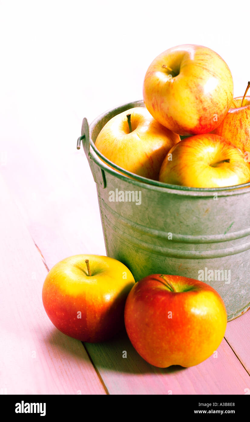 RED YELLOW APPLES IN RUSTIC BUCKET ON COLOUR WASH WOODEN BACKGROUND - Stock Image