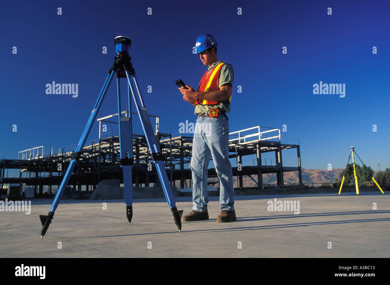 surveyor using GPS surveying unit at construction site in San Jose