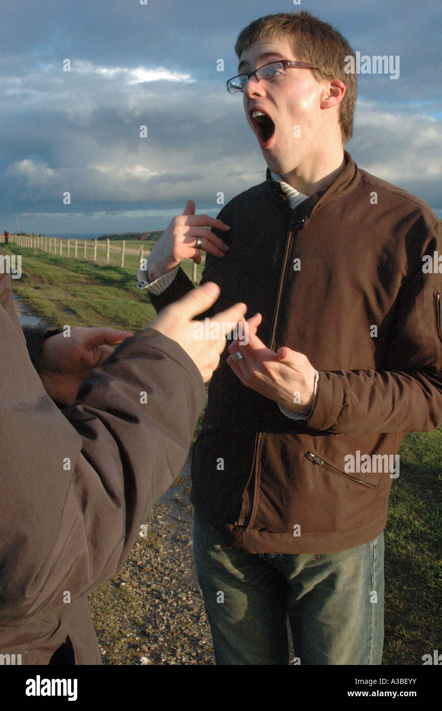Two men having a conversation in British sign language in the countryside - Stock Image