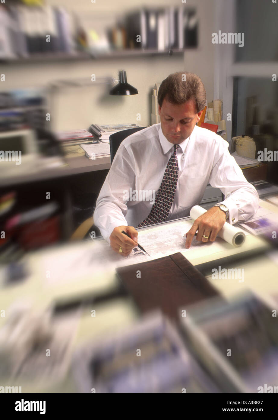 Architect drawing blueprints with blur - Stock Image