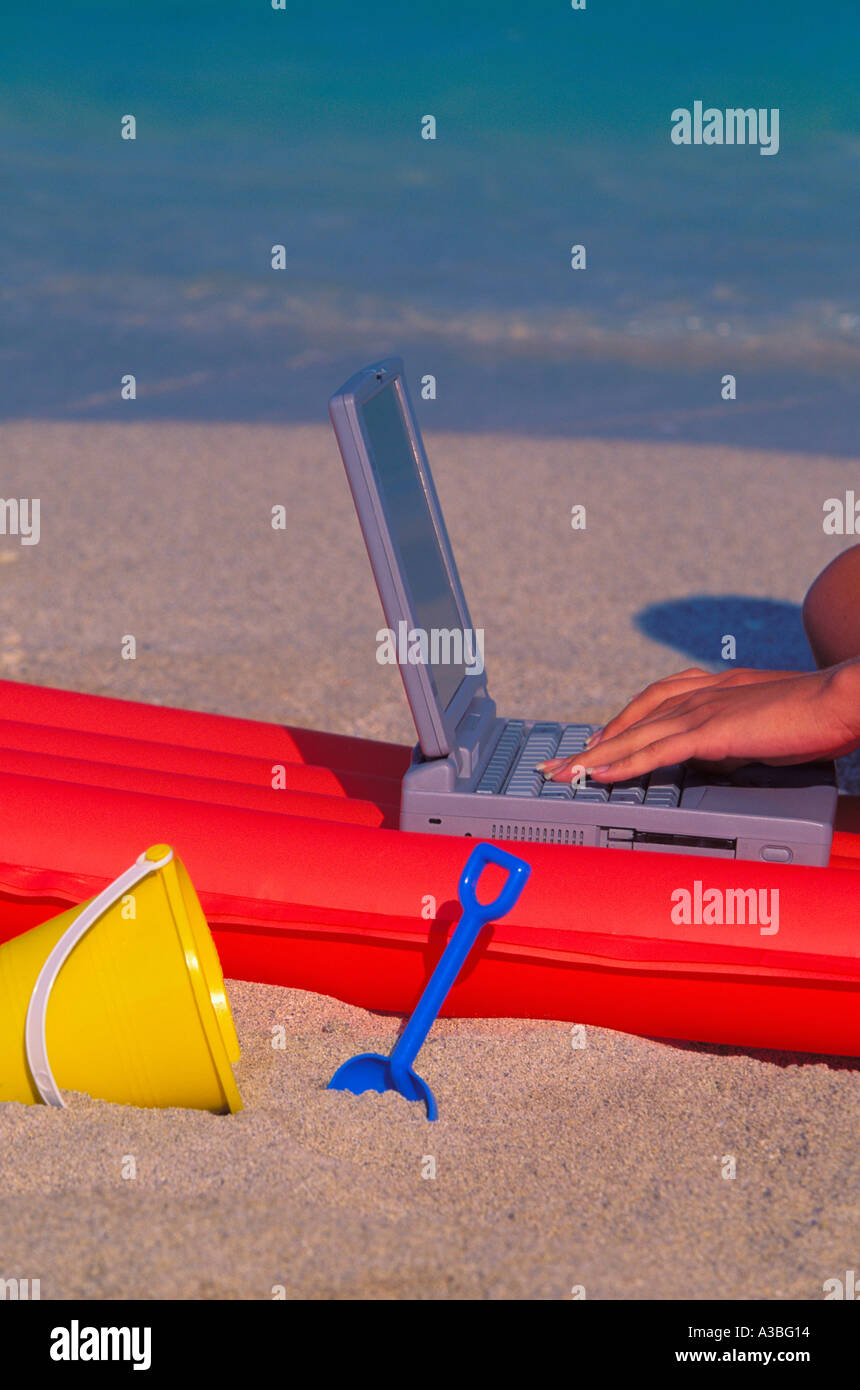 Hand typing on Notebook computer with floating mattress and beach toys by the beach 2803 015 22 - Stock Image