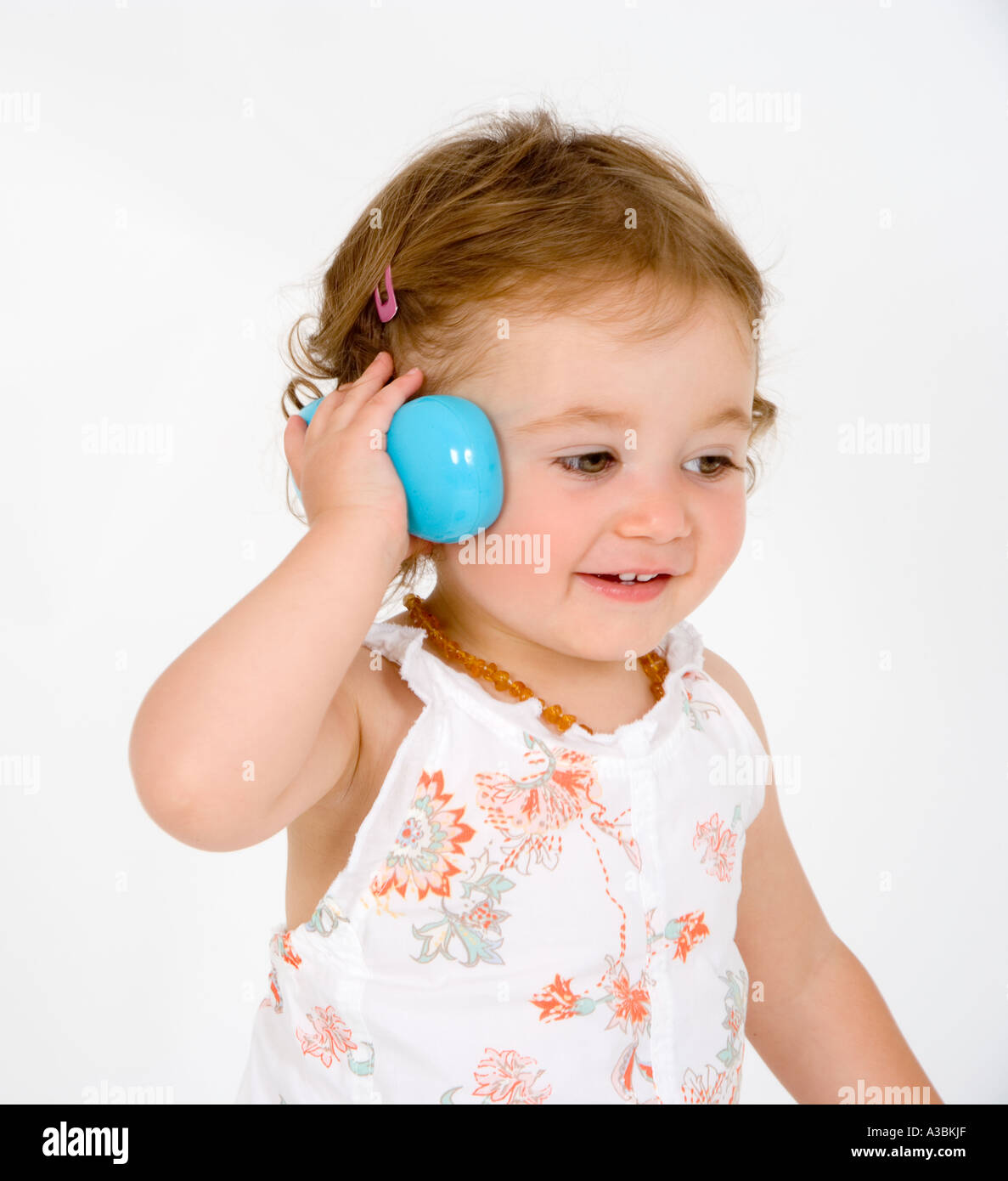 13a00eccb Female toddler (18-24 months) holding toy phone - Stock Image