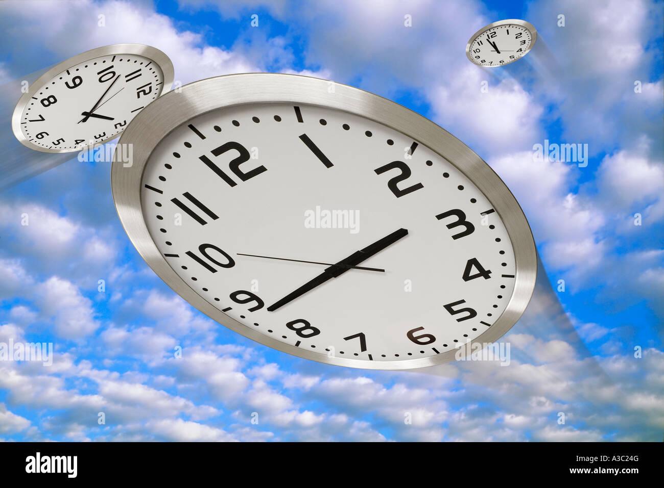 Clocks racing across the sky portraying the slogan Time Flies - Stock Image