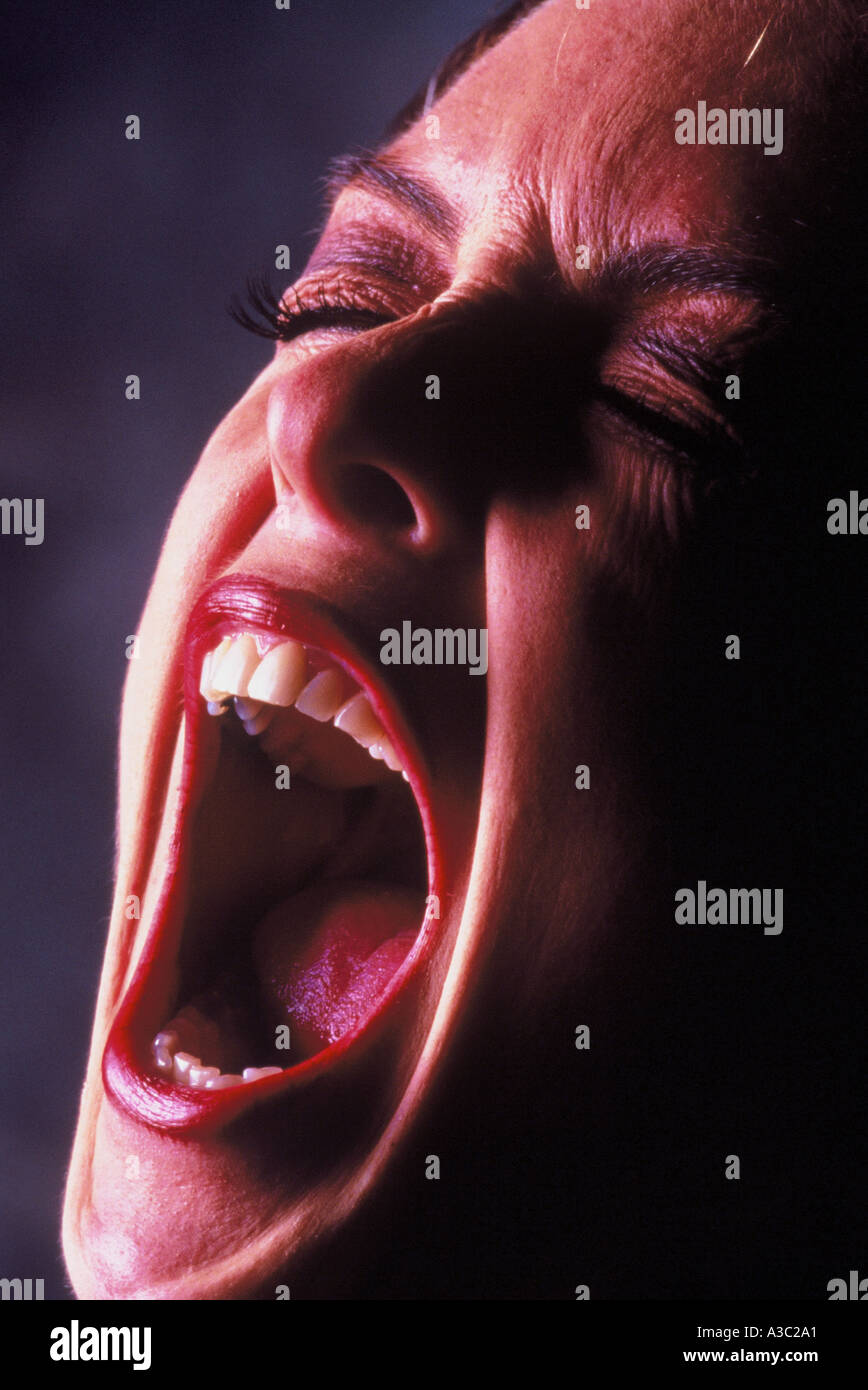 Close up portrait of a woman face in the act of screaming Stock Photo