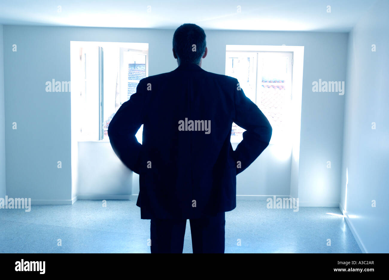 Man standing in an empty room / apartment / house - rear view silhouette - property / owner/ selling / rental / - Stock Image