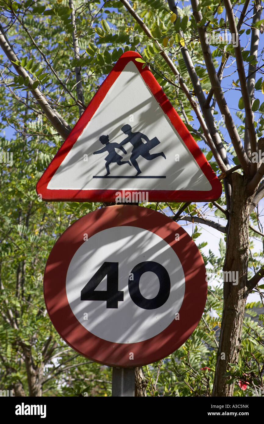 european style triangular red warning children crossing and 40 km h round speed traffic signs in trees - Stock Image