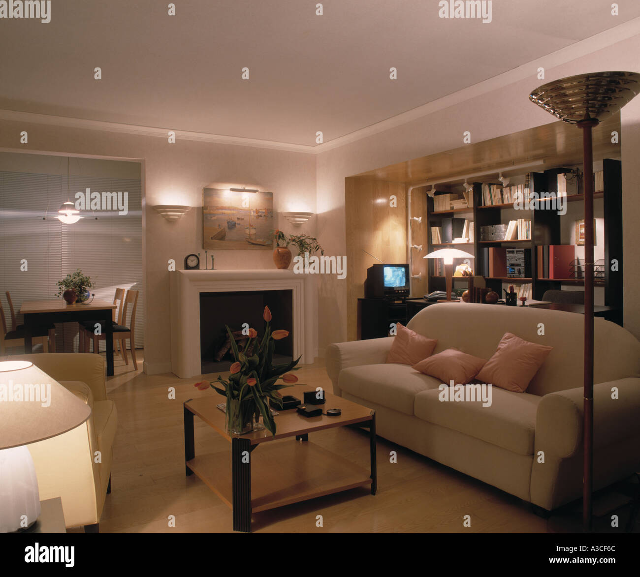 Cream sofa and lighted lamps and wall lights in modern living room ...